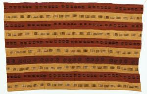 Image of Mud cloth with cowrie shells against maroon and mustard colored background