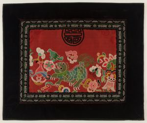 Image of Fragment of garment or purse made into table mat with frolicking lion amidst lucky symbols and flowers
